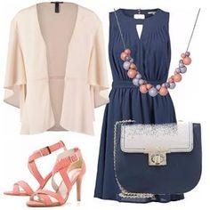 Vestito elegante blu navy, giacca aperta dal colore tenue, sandali con il tacco rosa salmone, collana con le pietre lilla e rosa in tinta con le scarpe e mini borsa a tracolla blu e panna.