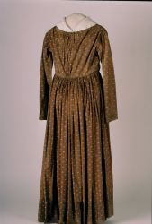 Woman's brown cotton work gown or dress printed with small white geometric flowers. Long straight sleeves, lined with blue resist cotton. Bodice gathered at shoulders and center front and back. Gathered skirt. Piping at waist, neck, and sleeve holes. No apparent means of fastening the dress in front.Probable Datecirca 1840