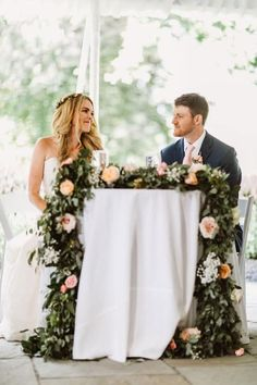 Bride and groom at sweet heart table with cascading garland. Peach and white wedding ideas.