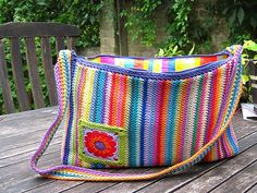 Vibrant vertical stripes on this crochet bag gives it a unique look. Love the motif used to embellish the front and the lining as well!