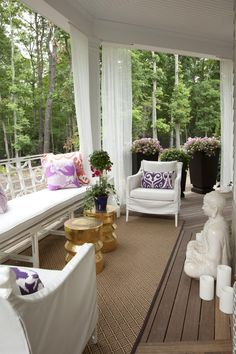 A white Buddha statue, among other Asian accents used throughout the space, introduces a Zen mood to this porch sitting area. Beautiful white furniture and sheer white curtains look even brighter against the natural background and neutral floor. Throw pillows add pops of accent color in red, purple and pink, while the pair of metallic tables adds a touch of glam to the design.