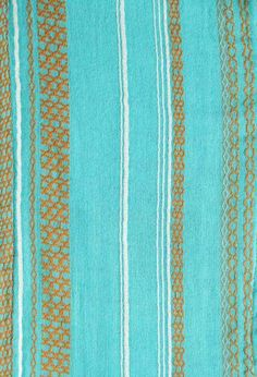 Closeup of Ace & Jig's Mineral print, featuring a teal backdrop and gold stripes that evoke a sun-kissed radiance.