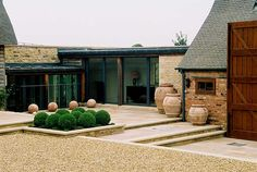 courtyard, simple elements of stone and buxus ball topiary - Large terracotta urns by Italian Terrace