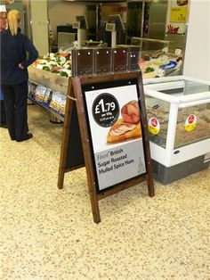 """Tesco Wooden Poster A-Board  Developed by Assigns especially for Tesco, this A-Board unit holds two 30"""" x 20"""" posters and has a specially designed header that merchandises leaflets advertising cook in sauces and brands elewhere in the store."""
