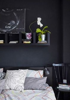If you don't even have room for a nightstand, a LACK shelf unit mounted above the bed can do the trick, without taking up any floor space at all. (Also of note, we especially love how this bedroom, from IKEA, made the shelf nearly disappear with a black-on-black look. Super chic.)