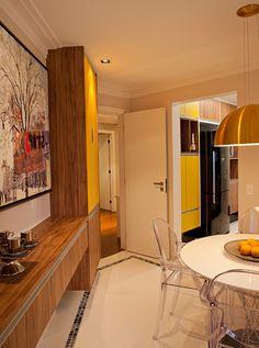 Atendo os pedidos das clientes, foi utilizado o laminado em madeira e vidros amarelos, bem como armários que pudessem ser usados como aparador, que trouxeram alegria e modernidade ao espaço.