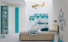 This breezy aqua and white color scheme, with yellow accessories, would suit either a boy or a girl. A corrugated feature wall adds texture to the predominantly white room, and a cluster of framed pictures makes things look homey. Stepped display shelves keep collections in check and looking stylish.