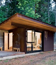 """On a four-acre site on Salt Spring Island, just southwest of Vancouver, Olson Kundig crafted a cabin—modest in size yet bold in design—on the site where another cottage once stood. Inside the walls of rammed earth and steel, the 191-square-foot space is a cozy nook warmed by the caramel colors of the cedar on the floor and ceiling, which was milled from salvaged timbers, as well as the heat produced by the wood-burning stove. """"The small size creates an intimate, protected refuge within a ..."""