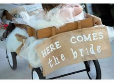 """Rustic Vintage Wedding.  Rustic sign on burlap """"Here comes the Bride"""" hanging on the back of the wagon that the ring bearer and youngest flower girl rode in down the aisle right before the bride walked down the aisle."""