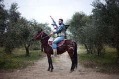 GIORGOS MOUTAFIS / AFP / GETTY IMAGES  A rebel poses mounted on his steed near the Turkish border in northwestern Syria on March 16, 2012.
