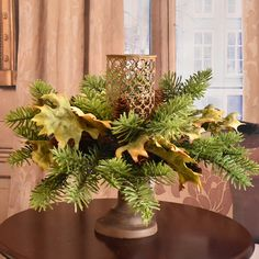 Display this lovely pedestal candle holder in your home for fall  and thru the holidays.  Artificial pine and soft tan oak leaves encircle a metal open weave cylinder.   Perfect for decorating. Only use with a battery operated candle for safety. ( candle not included)