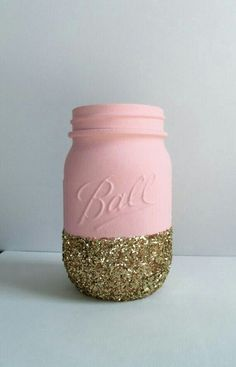 Pink and Gold Minnie Mouse first birthday party DIY flower vase idea: Pink painted mason jar dipped in gold glitter. These are great for a cream colored flower arrangement. Wondering how to make them? Check out this video (you can YouTube DIY Glitter Mason Jars) https://www.youtube.com/watch?v=24aVf_hani0 For more ideas, visit A Pop of Party!