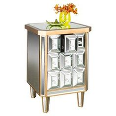 "Mirrored side table with faceted drawer fronts and golden trim.  Product: ChestConstruction Material: Mirrored glass and woodColor: Gold Dimensions: 26"" H x 18.5"" W x 18"" D"