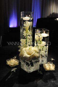 This arrangement would cost about $35 to DIY using round vases.       Supplies: 3 vases, 2 votive candles,  2 floating candles, cellophane, 6 calla lilies, and 2 orchids (alternatively we could use snapdragons).