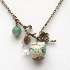 40mm antique brass leaf pendant, 8mm green jade round bead, quartz teardrop bead, 16mm porcelain owl pendant, antiqued brass chain.