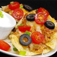 Homemade chicken enchilada sauce flecked with chile peppers is spooned over tortilla chips in this tasty recipe for chicken enchilada nachos.