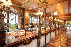 Laduree on the Champs-Elysees, Paris.  One of the most visually beautiful luxury tea houses/cafe bakery in the world, or at least the part of the world I've visited.  The tasty treats are out of this world too.  I've been there pre fire rebuild but it looks pretty much the same.