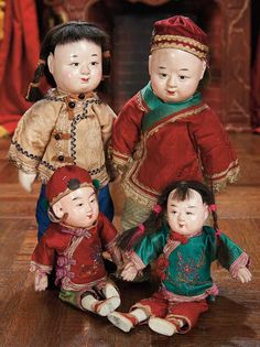 "Four Chinese Composition Child Dolls in Original Costumes 7"" (18 cm.) and 9"". The four dolls have composition heads with"