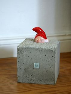 "Love this site... too bad it's in another language.  Cute idea to put a toy ""peeking"" out of a block of cement!!"