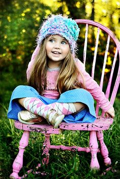 A beautiful child in a pink chair. The color pink represents compassion, nurturing and love. It relates to unconditional love and understanding, and the giving and receiving of nurturing. Pink is feminine and romantic, affectionate and intimate, thoughtful and caring. It tones down the physical passion of red replacing it with a gentle loving energy.