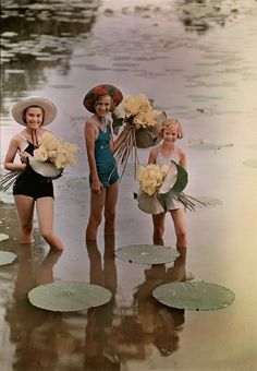 Girls standing in water holding bunches of American Lotus, Amana, Iowa, November 1938. (Photograph by J. Baylor Roberts, via National Geographic Found)