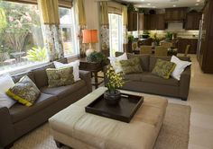Two brown sofas with yellow and brown patterned pillows with white pillows surrounding a large beige ottoman serving as a coffee table in an open concept home.
