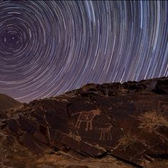 Teimareh Petroglyphs and Star Trails  Engraved in rock, these ancient petroglyphs are abundant in the Teimareh valley, located in the Zagros Mountains of central Iran. They likely tell a tale of hunters and animals found in the middle eastern valley 6,000 years ago or more, etched by artists in a prehistoric age. In the night sky above are star trails etched by the rotation of planet Earth during the long composite exposure made with a modern digital camera. On the left, the center of the…