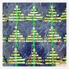 Arbolitos de Navidad que hicieron mis alumnos de 3ero de Preescolar con papel y un palito de madera, decorados con lentejuelas.