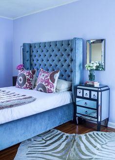 Chic bedroom, zebra rug, distressed mirror, blue velvet headboard, mirrored dresser