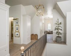 A Darlana Medium Lantern hangs from a shiplap ceiling over a second floor landing clad in pine wood floors lined with an iron staircase railing accented with brass finials while built in cabinets sit on either side of a hallway opening boasting three stacked gold leaf photos lit by a brass picture light.