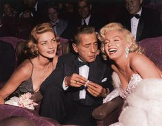 Humphrey Bogart with wife Lauren Becall as he clearly looks down Marilyn Monroe's dress.