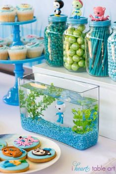 Octonauts themed birthday party with Such Cute Ideas via Kara's Party Ideas | Cake, decor, cupcakes, games, and MORE! Awesome dessert display. Love the tank with Barnacles, and the character topped jars.