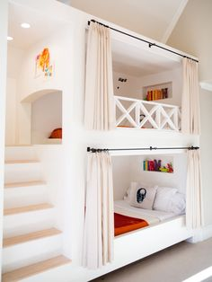 Bunk beds with stairs and curtains.