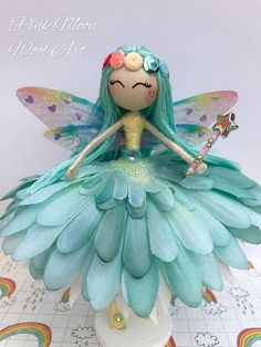 Pretty Blue Flower Fairy Doll named Marina, Miniature Fairy Ornament, Collectable Rainbow fairy Doll, would make a lovely Gift for Girls, Birthday Present, Guardian Angel. Pretty Fairy Cake Topper. Marina has handmade rainbow coloured wings, with glitter and hearts which captures the light. She holds a little beaded star wand, ready to make your wishes come true. She has a little rainbow sequin head dress. Her face has been hand painted. Marina is mounted on a little wooden stand and…