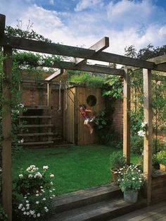 Simon Fraser designed this unique outdoor space featuring an arbor incorporating a child's play space.