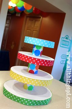 Cup Cake Stand- Thick cardboard tiers, covered with paper if needed, with ribbon edges.  Separate tiers with covered soup cans, with a low pinapple or cat food can underneath all hot glued for stability.