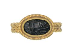 Ancient Roman intaglio ring. Set with an oval black glass intaglio engraved with a profile of a bust in a closed back cut down setting, framed by a row of intricate semi-circular engravings and set on a twisted gold wirework shank with central flat band. Yellow gold, 3.87g in weight, circa 1st – 3rd century AD.