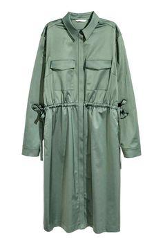 Платье-рубашка: Платье длиной до колена из хлопковой ткани с блеском. На платье воротник и потайная застежка спереди. Нагрудные карманы с клапанами и кулиска на талии. Длинные рукава с застежкой снизу. Без подкладки.