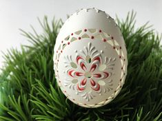 This is a duck egg pysanka in its natural white color. It is decorated using red and white wax. The front and the back of the egg has a flower design. The sides are decorated with a delicate lace design which surrounds the egg. The carvings and wax-embossed design mirror the delicacy of