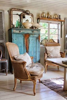 Eclectic Mix: industrial lighting, trophy shelf, gorgeous chippy blue cabinet, deconstructed French arm chairs, bottles, shutters...the list goes on.  WOW