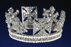 The George IV State Diadem  Made by Rundell, Bridge & Rundell (and likely designed by their designer, Philip Liebart) in 1820, the diadem features a set of 4 crosses pattée alternating with 4 bouquets of roses, thistles, and shamrocks. The motifs are set on a band of diamond scrollwork between two bands of pearls. Queen Alexandra had the diadem made smaller in 1902, reducing the top band of pearls from 86 to 81, and the bottom band from 94 to 88.