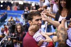 USA's Michael Phelps, left, holds his son Boomer after he won the men's 200-meter butterfly final during the swimming event at the Rio 2016 Olympic Games at the Olympic Aquatics Stadium in Rio de Janeiro on Aug. 9, 2016.