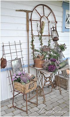 Porch display - trellis, metal chair, sewing machine base/table, wood crate, rake and pulley.