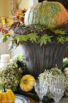 fall centerpiece with pumpkins, hydrangeas and pine cones