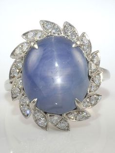 Platinum ring with an oval blue star sapphire at 13.12 carats and 28 round brilliant diamonds at 0.56 carat total weight VS1 clarity G color with milgrain detailing, circa 1950. Size 7.25. Appraised at $25,293.
