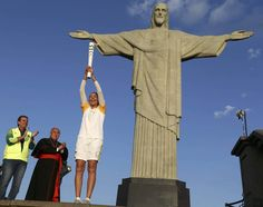 Former Brazilian volleyball player Isabel Barroso holds the Olympic torch next to Christ the Redeemer statue.