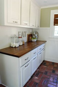 stained wood counter tops + white cabinets + brick floor = my dream kitchen :)