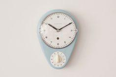マックス・ビルがデザインしたユンハンス社のキッチンクロックです。 1956年、氏が最初にデザインした時計でもあります。  ベビーブルーカラーの陶器製ボディにフラップカバー、ムーブメントはオリジナルの手巻き式になります。現行品のウォールクロックにも継承されている文字盤のデザインとその下に配置されたタイマーが印象的です。タイマーももちろん作動し、ジリリリリ・・・とベルの音で知らせてくれます。  当時のものとしてはコンディションは極めて良好で、フラップカバー、本体共に特筆すべきダメージは見受けられません。若干の日差はございますが調整機能も付いており、ムーブメントの動作も良好です。
