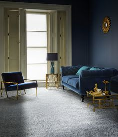 A grey carpet looks sublime against a navy backdrop with dark blue furniture and gold accessories