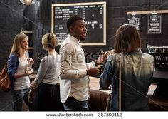Mixed race friends talking at the counter of coffee shop